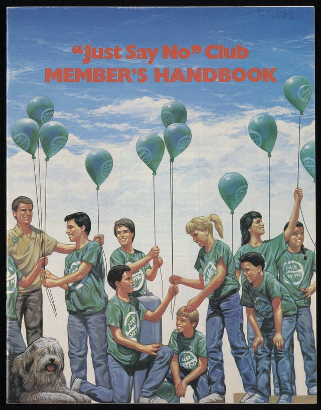 The front cover of the Just Say No Club handbook featuring an illustration of young children, all wearing blue jeans and green t-shirts, holding balloons with the Just Say No logo on them.