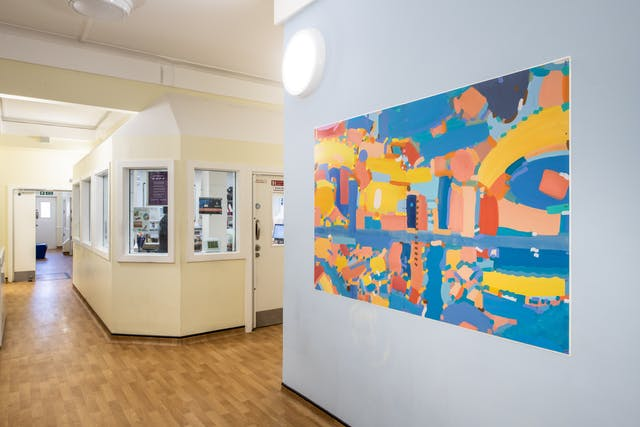 A photograph showing a corridor painted magnolia with wood laminate flooring. There is a high security internal office area surrounded by internal windows and a door. On the right-hand side of the image the wall is painted light blue and features a large rectangular canvas hung in landscape orientation. The canvas features a wide range of freely drawn irregular shapes in various tones of yellow, blue and orange. There are some straight, curved and even wavy lines. The abstract shapes resemble building, pathways, and rivers as though seen from a bird's eye view.