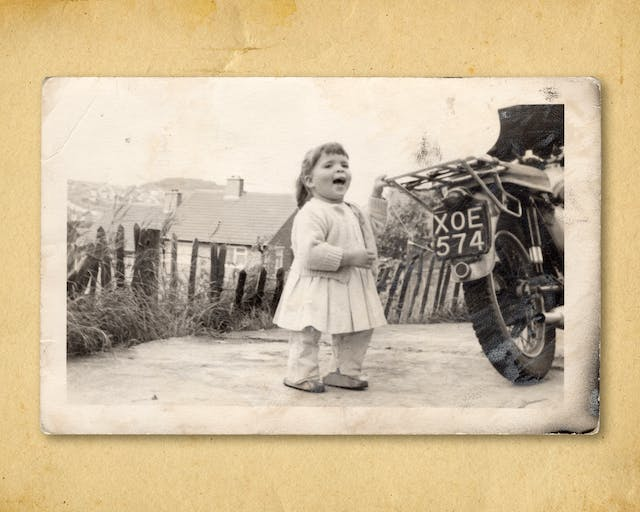 Photograph of a black and white photographic print, resting on a brown paper textured background. The print shows a small young girl in a dress, trousers and a cardigan standing outside. Her left hand is holding on to the pannier rack of a motorcycle which is just appearing into the frame. The motorbike has the registration plat
