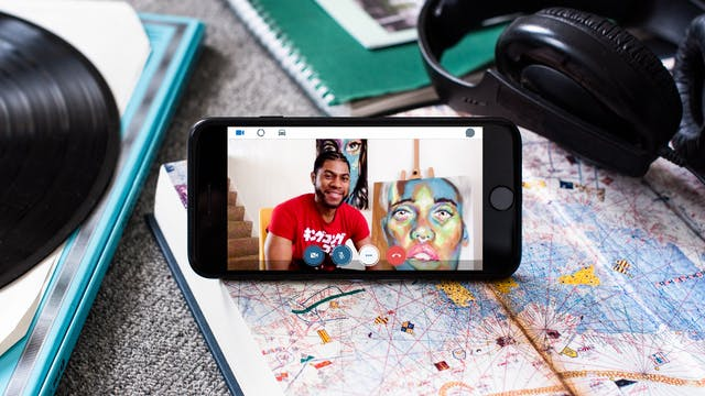 Photograph of a smartphone propped up on an open book displaying a map. On the screen is a video call with Alain 'Fusion' Clapham who is seated in a red t-shirt next to a colourful painting of a face. There is a red phone icon at the bottom of the screen. Plugged into the phone is a pair of black earbud headphones. The phone is surrounded by other books and notebooks on a carpeted floor.