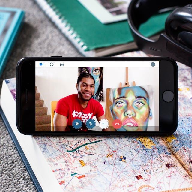 智能手机的照片在显示地图的一本开放书求职。在屏幕上是一个与Alain'Fusion'Claph的视频通话,坐在一件红色T恤旁,旁边是一张脸色彩色绘画。屏幕底部有一个红色手机图标。插入手机是一对黑色耳塞耳机。手机被其他书籍和笔记本在地毯的地板上包围。