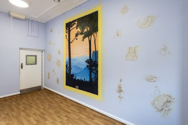 A photograph showing a room with a wood laminate floor, with a white door in which there is a small square glass window.  The walls are a light blue decorated with light gold looking textured prints of things such as suns, clouds, and shells each no bigger than 30 centimeters scattered across it. On the blue background there is a bright lemon yellow border in portrait orientation. Within the border there is a black silhouette of two trees with long trunks, one on the left and one on the right. They appear in the foreground together with silhouetted grass at the bottom of the frame. In the distance, different tones of blue make up a range of mountains and hills below. Above the hills, there is a light orange sky.