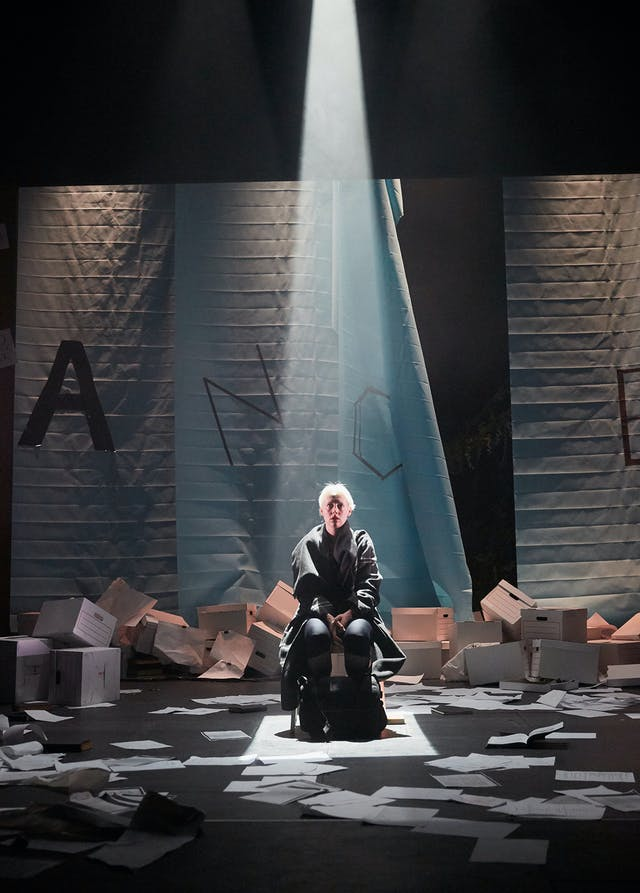 A woman sits ona  chair on s atge with spoltight beaming down on her from above. She's surrounded by a mess of cardboard boxes and loose sheets of paper.