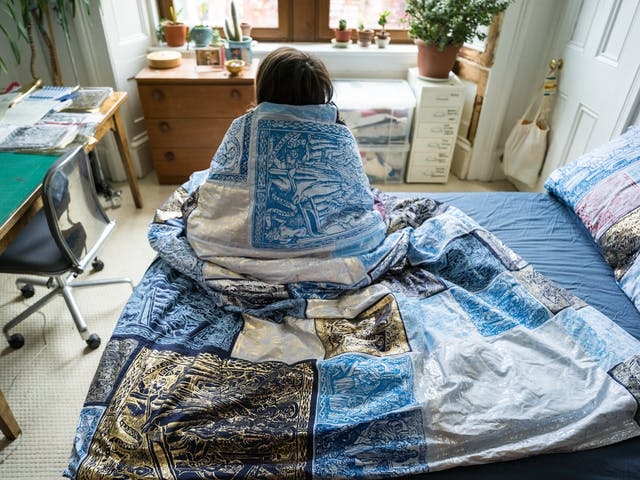 Photograph of a young woman sitting with her back to the camera on her bed, wrapped in a duvet cover made of a patchwork of blue, red, silver and gold screen-printed designs. She is looking towards large windows, a chest of drawers, a pot plant and the corner of a desk.