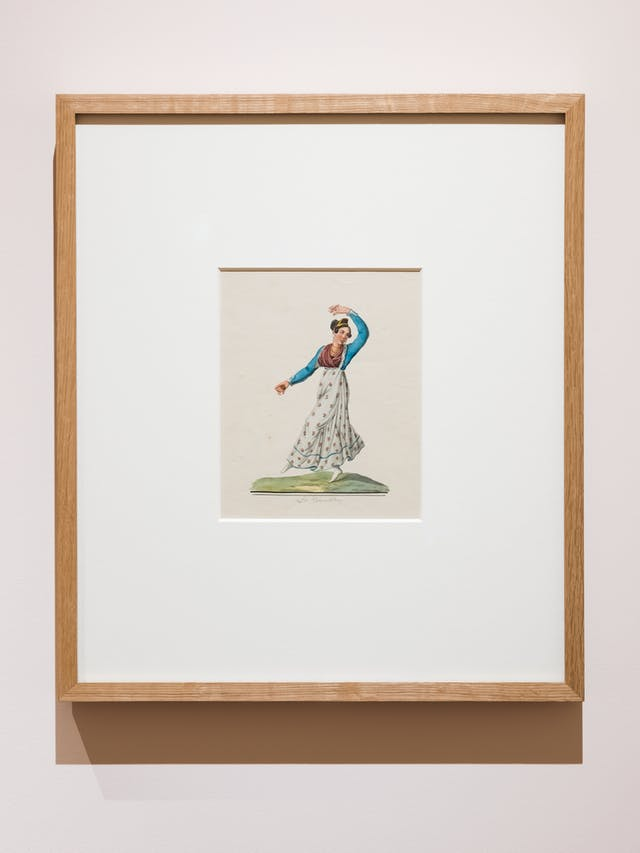 Photograph of an exhibition gallery showing a section of light pink coloured wall on which a framed print in a wooden frame has been hung. In a window mount within the frame is a colourful drawing of a woman dancing the tarantella, one arm raised over her head, one leg raised.