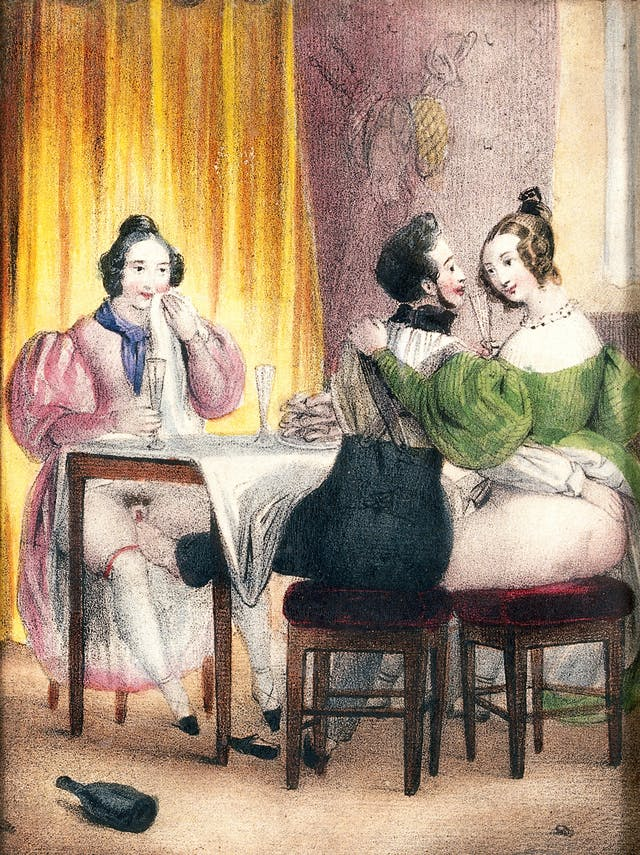While dining with two women, a man pleasures one of them with his foot. Coloured lithograph, c.1830