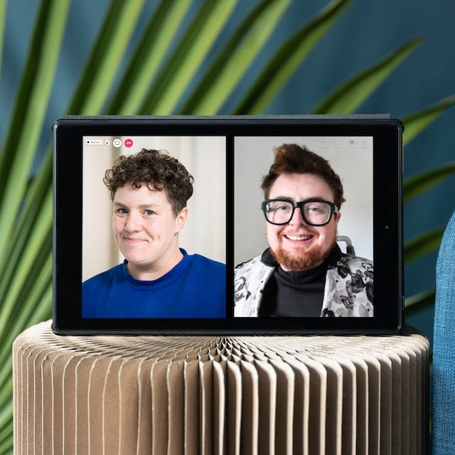 """Photograph of a tablet standing on a stool. On the left half of the tablet screen is a photographic portrait of Jess Thom, wearing a blue sweater.  On the right half of the tablet screen is a photographic portrait of Jamie Hale, wearing glasses and a black sweater with a patterned jacket over it. Also, on the screen are video call icons """"People"""", """"Chat"""" and a red telephone icon. There are green decorative palm leaves displayed in the background behind the tablet which is next to the edge of a blue sofa with a yellow cushion."""