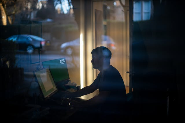 Photograph of a man through a glass window, sat at a desk in front of two computer screens. On the screen to his right are the words