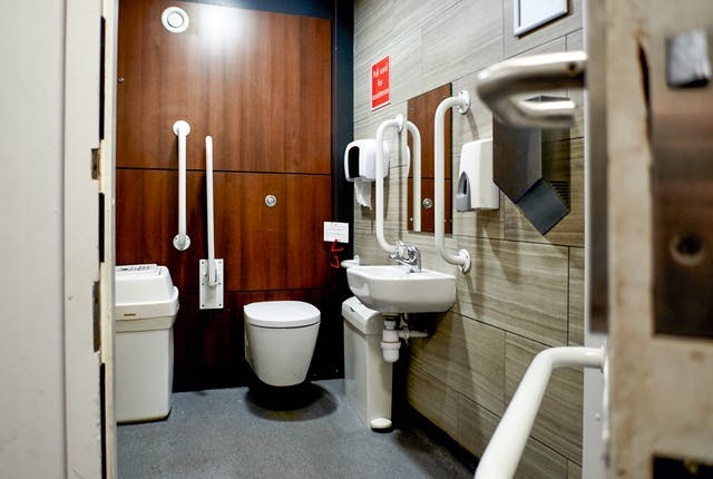 Photograph though the doorway of an accessible toilet showing part of the door and doorframe, along with the contents of the room, toilet, basin and sanitary bins. One of the walls has a wood effect panels and the room has a slightly modern feel.