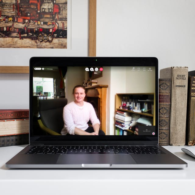 Tim Wingard appearing on a video call on a laptop screen. Tim is sitting in a chair in a light-coloured knitted jumper with tied up hair.  Tim is in a living room, sitting next to bookshelves with a fireplace in the background. Around the laptop on the desk are some old books and a wireless laptop mouse.