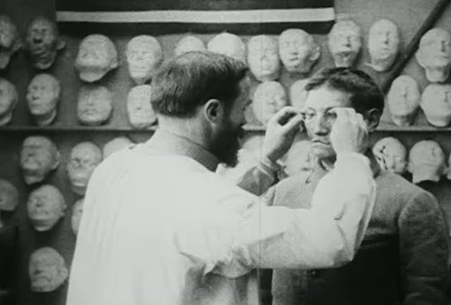 A man in a white coat adjusts the spectacles on another man