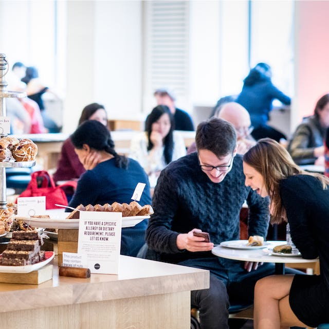 Photograph of a cafe scene with a table displaying cakes to the left of the image and people seated and chatting to the right and in the background.