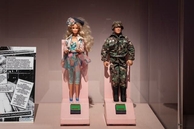 Photograph of an exhibition display case containing a male and a female doll. The female doll is dressed in floral outfit, the male doll is dressed in army fatigues. In front of each doll is a green button with the words,