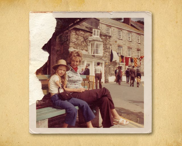 Photograph of a colour photographic print, resting on a brown paper textured background. The print shows a woman sitting on a public bench next to her young daughter. Behind them is large stone built building with a string of large naval flags hung across its facade. There are people in the distance walking toward the building. The mother and daughter on the bench are looking to camera. The daughter is wearing a summer brimmed hat and holding a hand bag in her right hand. The top left corner of the print has been torn such that the surface of the print and therefore the image have been lost.