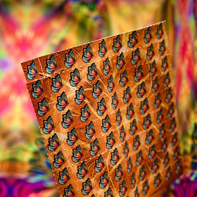 Photograph of a pretend sheet of LSD tabs with a butterfly motif, against a colourful abstract background.