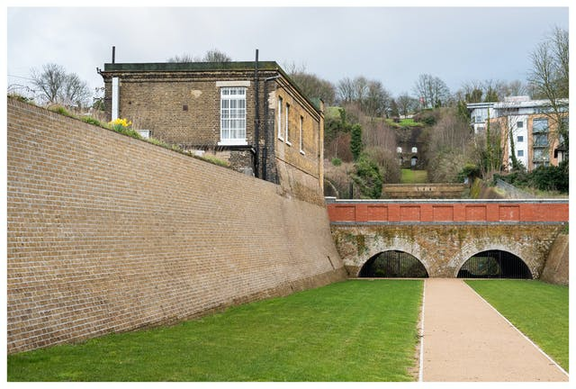 Photograph of a 19th century building with a high wall to the left of an area of grass with a path leading to a bridge. The sky is overcast, heavy with clouds and there are hills and modern buildings in the background. High on the wall is a lone bunch of bright yellow daffodils.