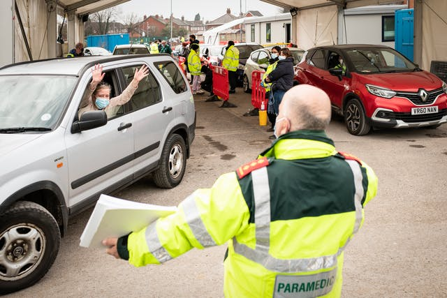 Photograph of a drive-through vaccination centre taking place in a car park. There are queuing cars waiting for the occupants