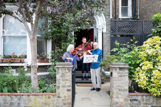 Photograph of the doorstep and front garden of a Victorian house. In front of the step and mother, father and son stand in front of a music stand playing the violin and flute.