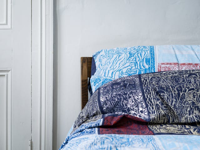 Photograph of a bedroom showing the left hand side of the headboard of a double bed, made up with a duvet cover and pillowcases which are made of a patchwork of blue, red, silver and gold screen-printed designs. To the left of the bed is part of a door.