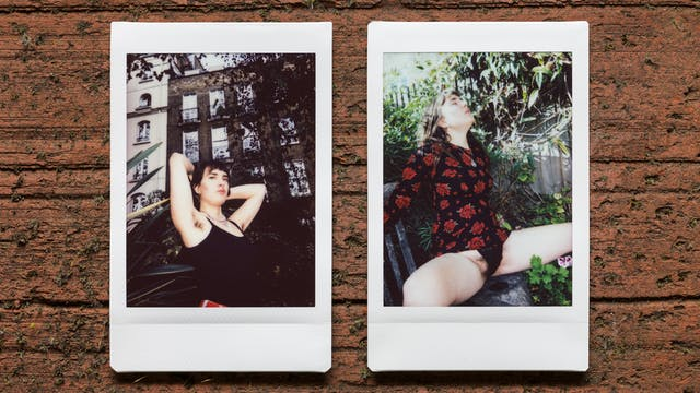 Photograph of two Instax Mini instant film prints in a line, resting on a textured brick surface. The two prints feature the same woman. The print on the left shows the her nestled within the branches and leaves of a tree outside a tall row of houses, with her arms raised up to show her armpit hair. The print on the right shows the same woman sitting in a garden scene with her clothes pulled up and her legs apart showing her black knickers and pubic hair.