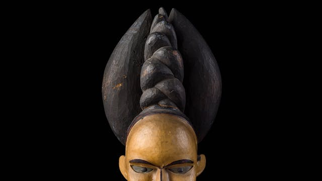 Photograph of the carved wooden head of a woman against a black background. On the woman