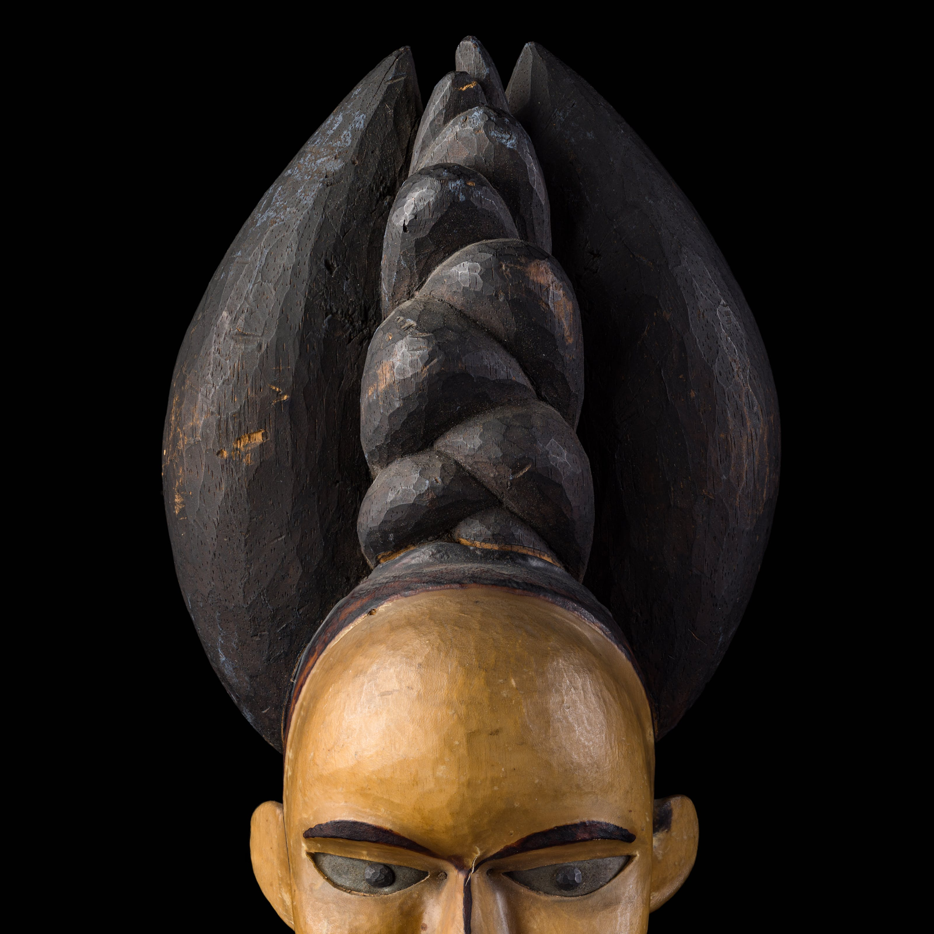 Photograph of the carved wooden head of a woman against a black background. On the woman's head is an elaborate headdress. The head is cropped by the bottom of the frame just below her eyes.