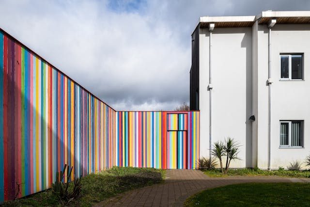 A photograph showing a tall, bright, colourful, striped perimeter fence of which each vertical slat is painted a different colour, consisting mostly of pastel blues, purples, yellows, and pinks. It runs along the left-hand side of the image towards the horizon where it meets a white rectangular looking building with two storeys, and a flat roof. Only one corner of the building is visible with two windows one above the other on separate floors. In the foreground there is short cut green grass, a path leading towards the building.