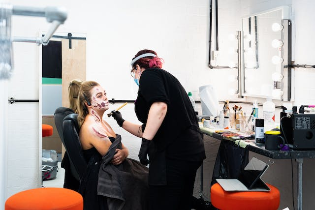 Photograph of a makeup area in a photographic studio with a mirror on the wall surrounded in light bulbs and a high table top beneath. A woman is sitting in a chair wrapped in a black towel with the early stages of prosthetic application on her face and shoulder. A woman in black, wearing a face mask and a visor stands over her with a makeup brush, applying makeup.