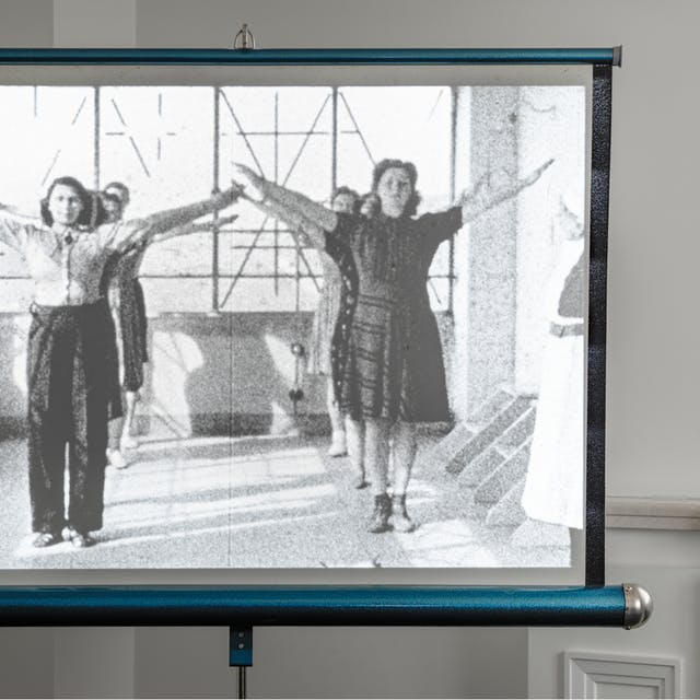 Photograph of a Hunter Starlight projector screen in the corner of room by a window recess. On the screen is an still from a film, showing two lines of expectant mothers with their arms raised as part of an excessive class. To the right of the frame a nurse is just visible.