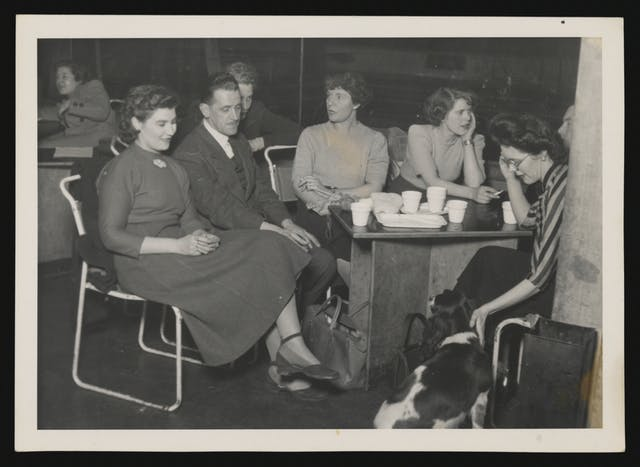 Black and white photograph showing a group of young men and women sitting around a table.