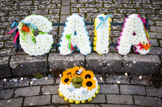 Photograph of flowers arranged into letters to spell the name Gaia, resting on brick paving.