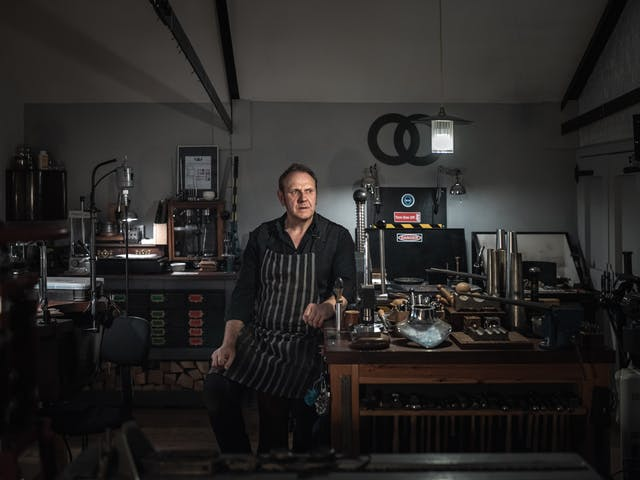 Photograph.  Portrait of a man sitting on a stool in his workshop.  His arm is leaning on a wooden workbench on which there are tools including a row of hammers and various other metal working tools.
