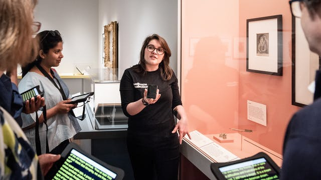 Photograph of a Visitor Experience Assistant conducting a speech to text tour of an exhibition at Wellcome Collection. She is talking into a phone whilst the visitors read a transcription of what she is saying from a tablet screen.