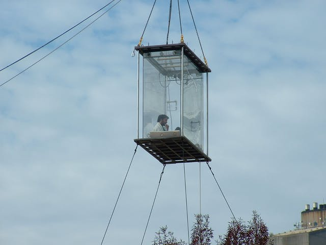Colour photograph showing a man sitting inside a clear box suspended in the air.
