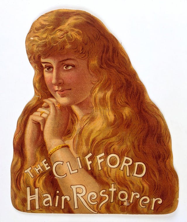 A die cut card showing the upper half of a smiling young woman with a profusion of golden hair and her hands raised to her chin.  Accompanying text reads