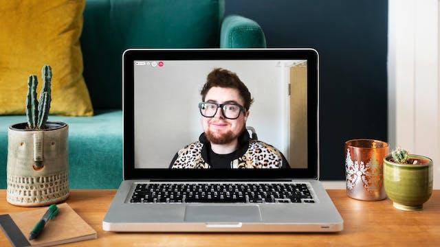 桌上放着一台打开的笔记本电脑,屏幕上显示着艺术家杰米·黑尔的形象