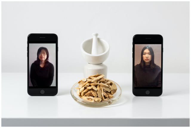 Photograph of a white, slightly glossy self against a white wall. On the shelf standing upright are two smartphones. On the screen on the left hand phone is a portrait of an older woman dressed in black from the waist up looking to camera. On the screen on the right hand phone is a portrait of a younger woman dressed in black from the waist up looking to camera. Between the two phones is a glass dish containing chopped astragulus root. Behind the dish is a white pestle and mortar.