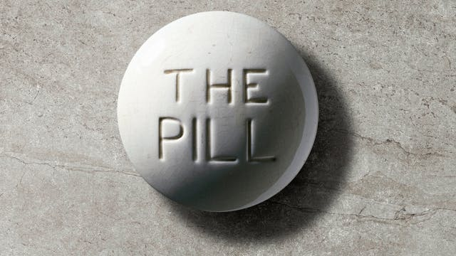 "Photograph of a contraceptive pill model, Europe, c. 1970. White crackled glaze, with debossed ""THE PILL"" text in centre, on a grey concrete textured background."