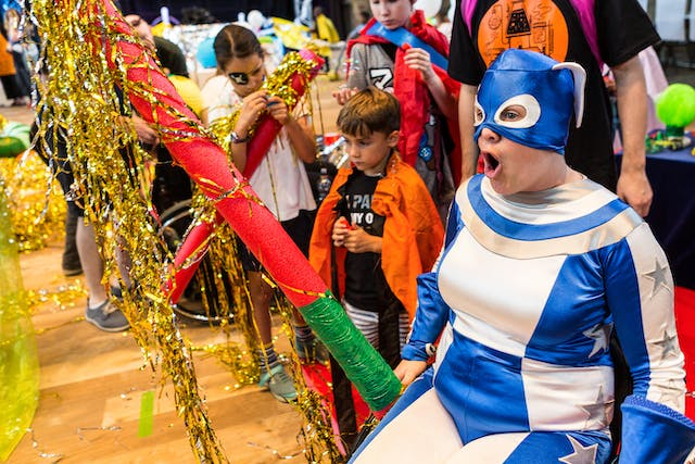 Photograph at an event showing a woman wearing a blue and white superhero style outfit, with her mouth wide open. She is accompanied by children involved in the activity.