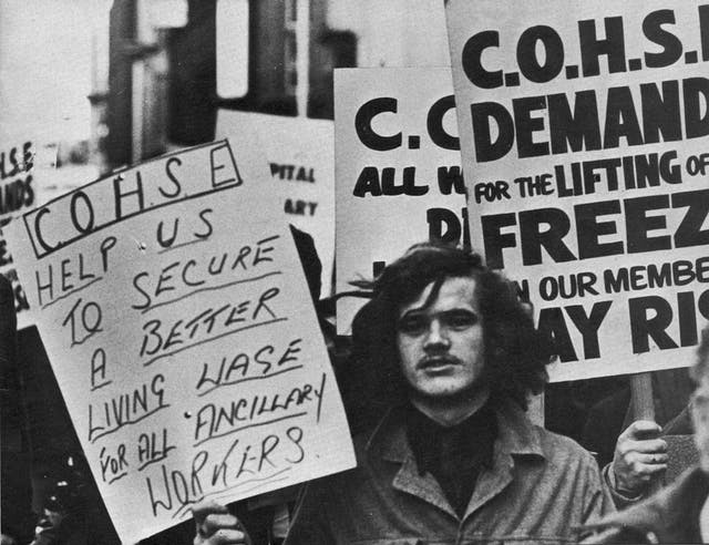 "Black and white photograph of a protest with banners reading ""COHSE help us to secure a better living wage for all ancillary workers"" and ""COHSE demand for the lifting of freeze on our members"