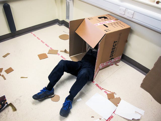 A photograph showing the corner of a magnolia painted room with lino flooring on which a long strip of fragile parcel tape has been stuck. Against the wall a large open cardboard box lays on its side out of which a young person wearing dark blue dungarees and blue trainers can be seen laying on their back, head concealed inside the box, knees bent upright and feet planted on the ground. Cardboard cut into shapes, and paper are scattered around the floor.