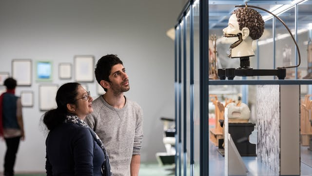 Photograph of a man and a woman looking at an exhibit in the Teeth exhibition at Wellcome Collection.