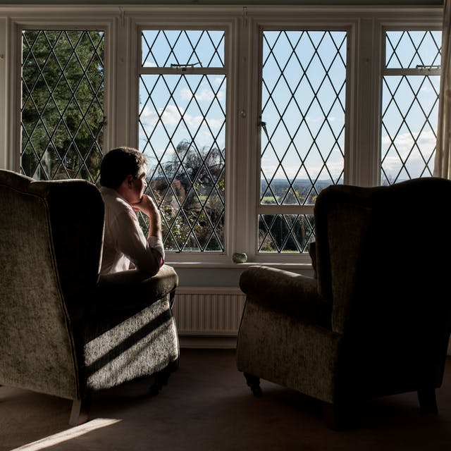 Photograph of a man sat in a living room armchair looking out of a window, his chin resting on his hand. To his right is an identical armchair which is empty,