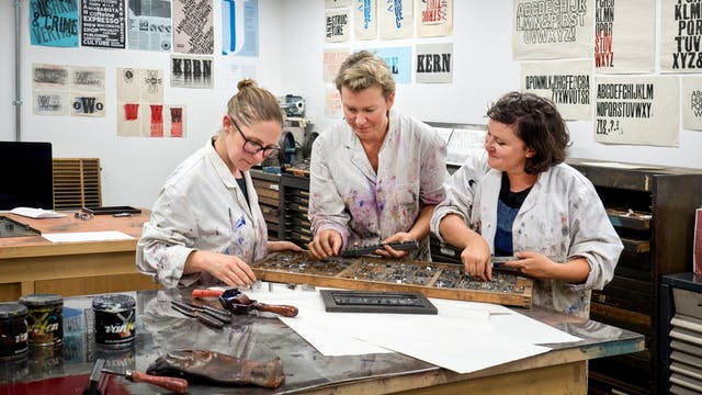 Photograph of Clare Qualmann, Amy Sharrocks and Madeleine Hodge working in the printmaking studio at London Metropolitan University.