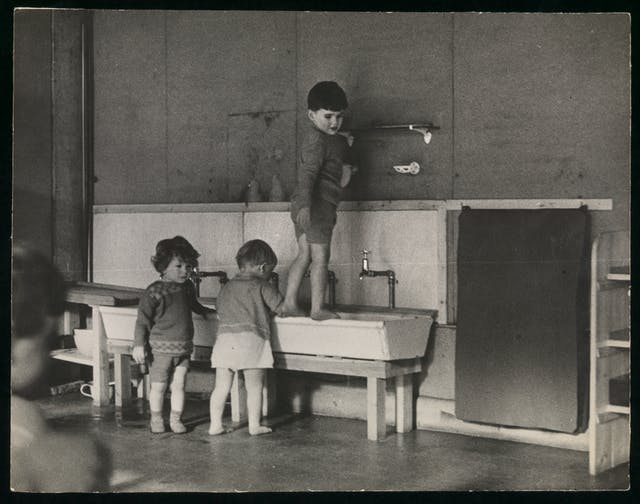 Black and white photograph showing three toddlers at a long, low wash basin.