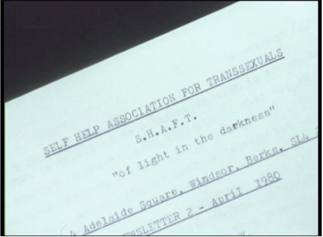 """Film still featuring a close-up of a paper document with typewritten text: SELF HELP ASSOCIATION FOR TRANSSEXUALS/ S. H. A. F. T./ """"of light in the darkness""""/ Adelaide Square, Windsor, Berks, SL4/ Newsletter 2 - April 1980"""