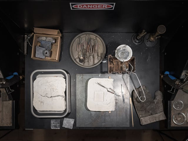 Photograph of instruments required to make the lead healing plate laid out on a workbench.  In the top left is a box containing raw lead.  In the centre us a dish of pliers, to the left is a ceramic bowl in the grip of a pair of tongs.  Inside the bowl is solidified lead, ready to be reheated.  to the bottom are two plaster-cast moulds, one of which is broken. The shape of the mould shows the imprint of a square.  In the bottom right there is a large heat-proof glove.  On the hood above the tools is a sign reading