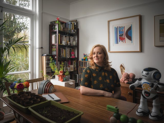 Photographic portrait of a woman in a white dining room, with her arm perched on the table.  Surrounding her are various child's toys including a robot, a small wooden crocodile and a pink fluffy octopus. There are picture frames on the wall in the background to the right of the frame, a set of shelves with CDs, and some house plants to the left of the frame.  In the foreground to the left, there is a tray of seedlings.