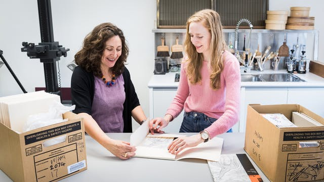 Photograph showing two female conservators standing at a workbench in a museum conservation studio. They are both in the process of carefully opening an archive folder containing a sketch book. To the left and right of them on the workbench are two open cardboard boxes also containing archive material. Behind them part of a photographic copy stand can be seen and a sink area covered in tools and brushes.