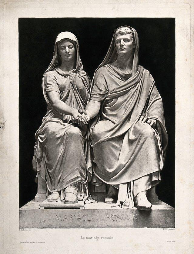 Black and white photograph of a seated couple in Roman dress, holding hands.